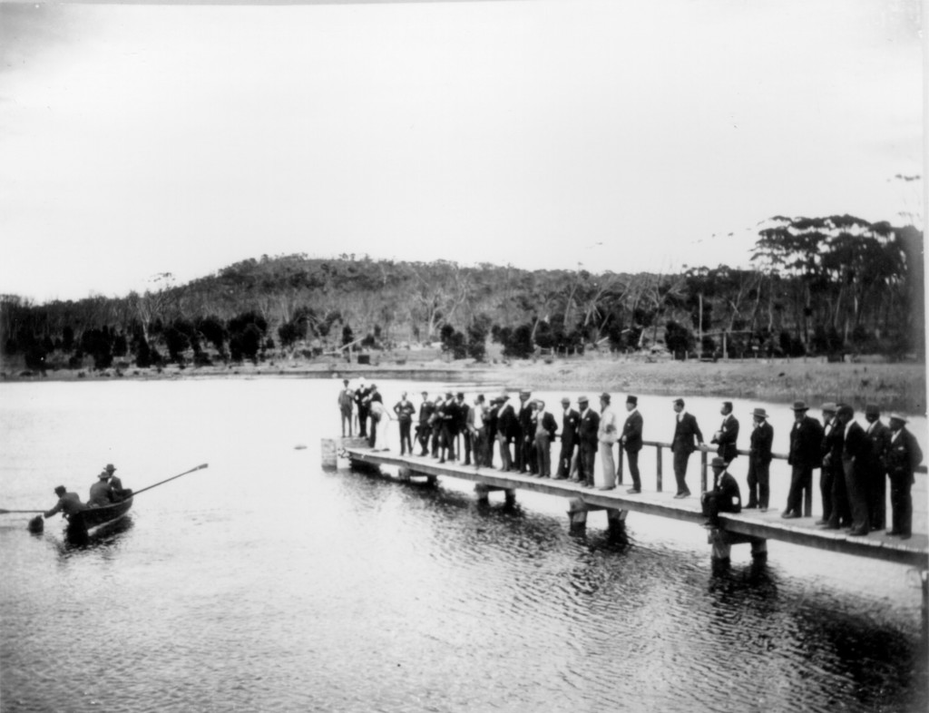 Watched by a party of officials, Premier Leake and others row across the reservoir 1902. , c. 1902.