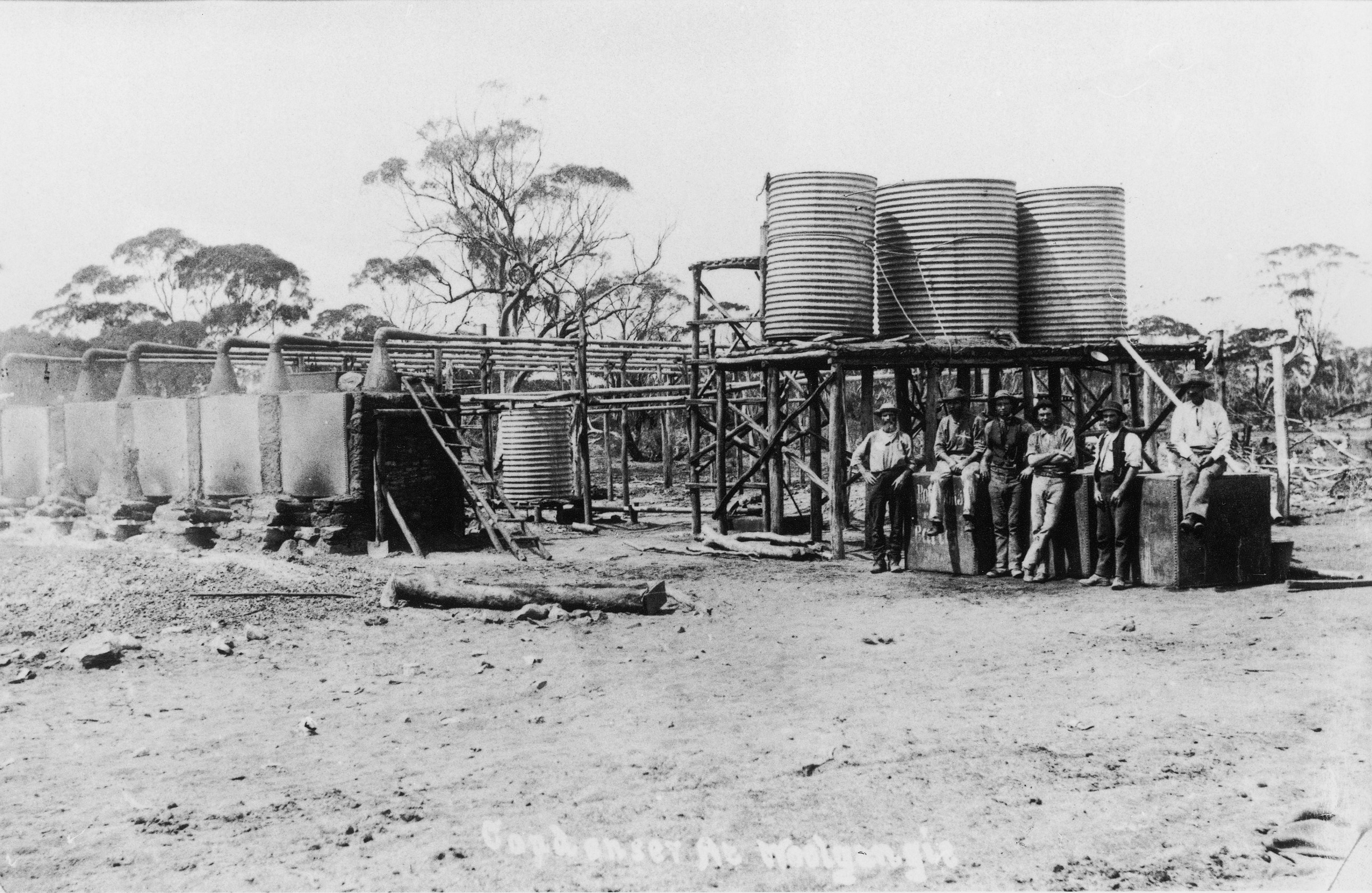 The workers standing in front of tanks used to boil water to generate steam which was condensed back into drinking water.